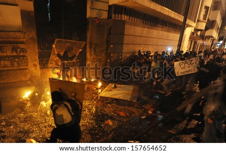 RIO DE JANEIRO, BRAZIL - OCTOBER 08: Black Bloc protesters throw molotov cocktails against the Chamber of Counselors municipal building during schoolteachers demonstrations demanding better wages on October 8th, 2013 in Rio de Janeiro, Brazil.
