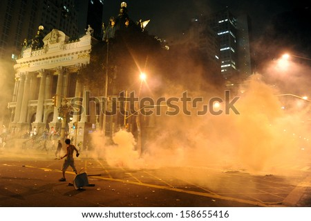 RIO DE JANEIRO, BRAZIL - OCTOBER 15: demonstrators surrounded by tear gas along the city center main avenue, Rio Branco and next to the Municipal Theater, during demonstrations in support to the teacher's strike as the annual October 15 Teachers' Day holi - stock photo