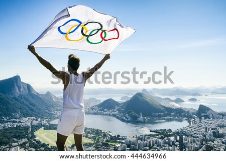 RIO DE JANEIRO - MARCH 21, 2016: Athlete stands holding Olympic flag above a city skyline view of Corcovado Mountain and Zona Sul.