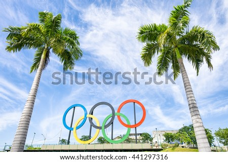 RIO DE JANEIRO - MARCH 18, 2016: Olympic rings stand under tall palm trees in a park in the North zone city suburbs.