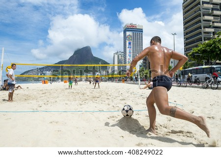 RIO DE JANEIRO - MARCH 17, 2016: Young Brazilian men play a game of futevolei (footvolley), a sport that combines football and volleyball, on the beach in Leblon.  - stock photo