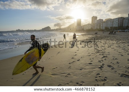 RIO DE JANEIRO - OCTOBER 30, 2015: A Brazilian surfer heads to the sea as a group plays the popular sport of keepy uppy on the shore of Copacabana Beach at sunset.