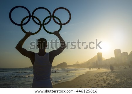 RIO DE JANEIRO - OCTOBER 30, 2015: Athlete holds Olympic rings above sunset city skyline view of Copacabana Beach in anticipation of the city hosting the Summer Games.