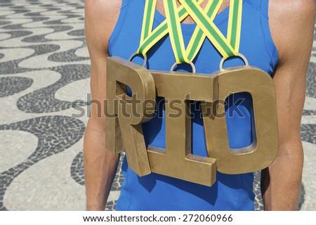 RIO first place athlete wearing gold medals standing outdoors on Copacabana Beach Rio de Janeiro Brazil  - stock photo
