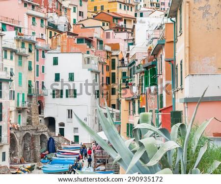 Riomaggiore, Italy - April 23: Cinque Terre, hillside village, Riomaggiore, stacked homes of different colors lead down where tourists enjoy unique atmosphere on April 23, 2011 in Riomaggiore, Italy. - stock photo