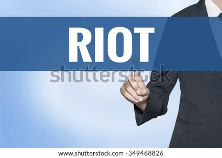Riot word on virtual screen touch by business woman blue background - stock photo