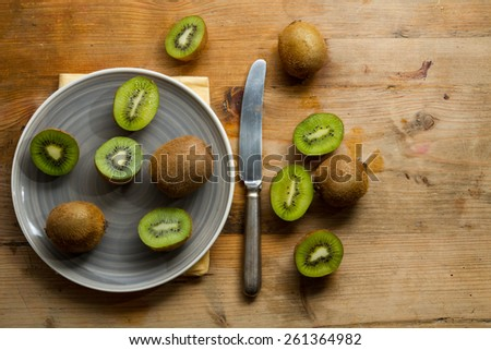 Ripe and half kiwi fruits on grey plate against a rustic wooden background. - stock photo
