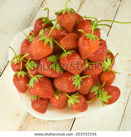 ripe and tasty strawberries on plate closeup - stock photo