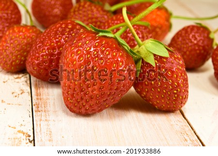 ripe and tasty strawberries on wooden table closeup - stock photo