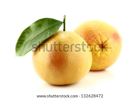 Ripe appetizing grapefruit with leaf on white background.