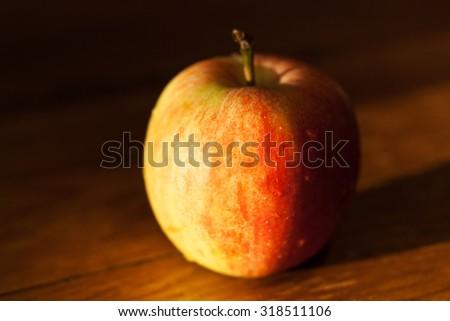 ripe apple fruit on wooden table illuminated by afternoon sunbeam - stock photo