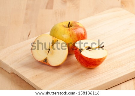 Ripe apple fruits and knife at old wooden table - stock photo