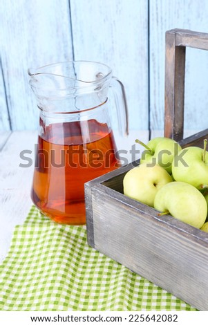 Ripe apples and juice in basket on table close-up - stock photo