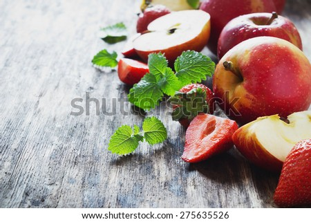 ripe apples and strawberries on old wooden table. fresh fruit from the garden. health and diet food. copy space background - stock photo