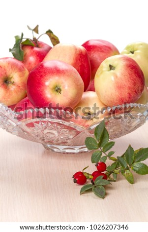 Ripe apples in a crystal vase and rose hips on white background