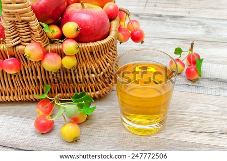 ripe apples in a wicker basket and a glass of apple juice on a wooden background. horizontal photo. - stock photo