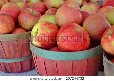 ripe apples in bushel baskets at the market - stock photo