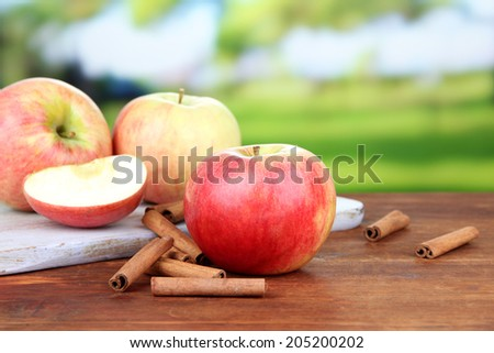 Ripe apples with cinnamon sticks  on  wooden table, on bright background - stock photo