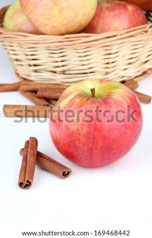 Ripe apples with with cinnamon sticks isolated on white