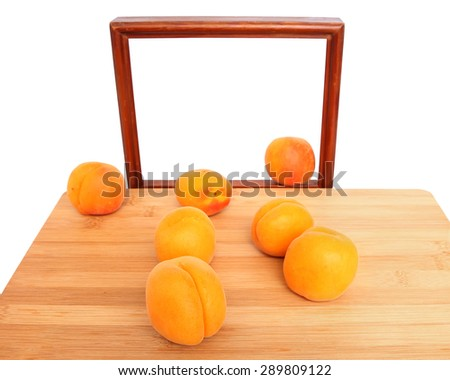 Ripe apricots fruit on a wooden cutting board with picture frame in the blur background. Selective focus on the foreground. Natural blur in background.Art of healthy natural food. Fruit nature design - stock photo