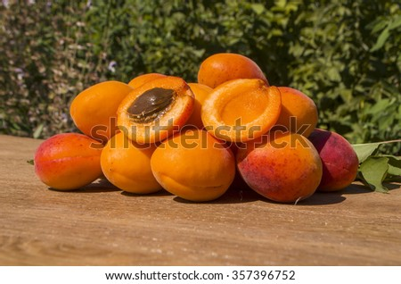 Ripe apricots on green background. Fresh apricots and linen cloth on a wooden table - stock photo