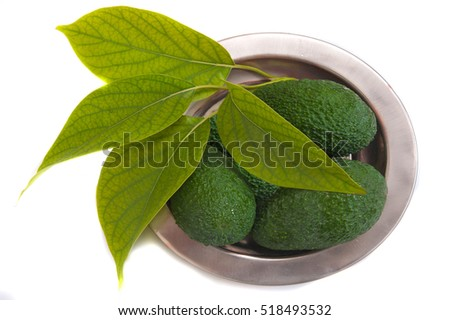 ripe avocado with leaves in plate on white background