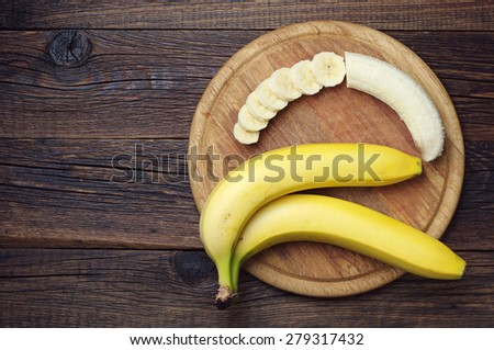 Ripe bananas and a sliced on wooden cutting board, top view - stock photo
