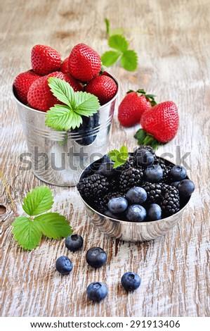 Ripe berries, blueberries, strawberries, blackberries in gardening buckets, summer harvest. Fresh vitamins, vintage rustic background, selective focus, toned image - stock photo