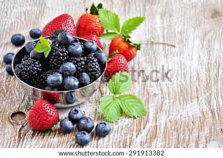 Ripe berries, blueberries, strawberries, blackberries in metal bowl, summer harvest. Fresh vitamins, vintage rustic background, selective focus, toned image - stock photo