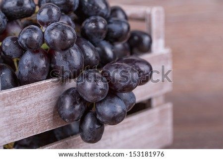 Ripe black grapes on a wooden background - stock photo