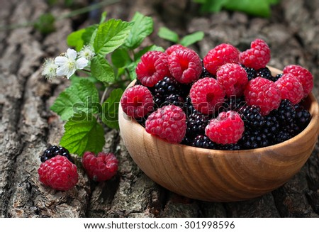 Ripe blackberries and raspberries in wooden bowl. Selective focus - stock photo