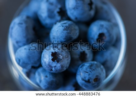 ripe blueberries in a glass on a dark stone background - stock photo