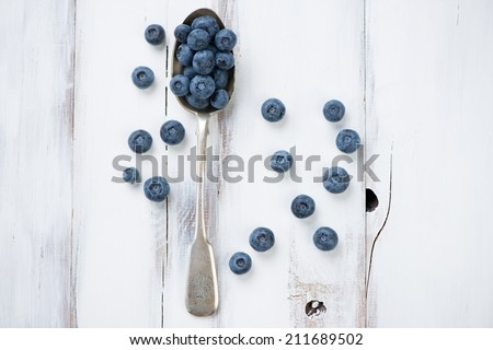Ripe blueberries in a spoon over white wooden background - stock photo