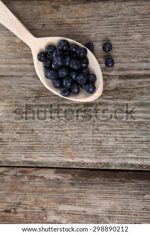 Ripe blueberries in a wooden spoon on the table