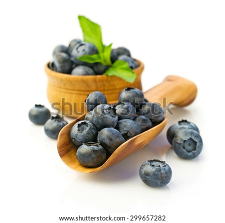 Ripe blueberries in wooden scoop, isolated on white - stock photo