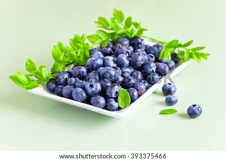 ripe blueberry with leaves on a kitchen table