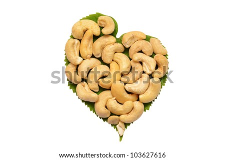 Ripe cashew nuts with leaves on a white background