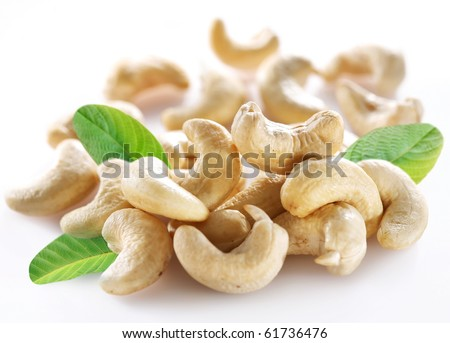 Ripe cashew nuts with leaves on a white background. - stock photo
