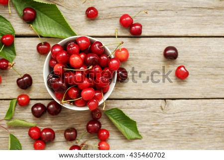 Ripe cherries in bowl on a grey wooden table - stock photo