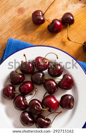 Ripe cherries on rustic wooden background - stock photo