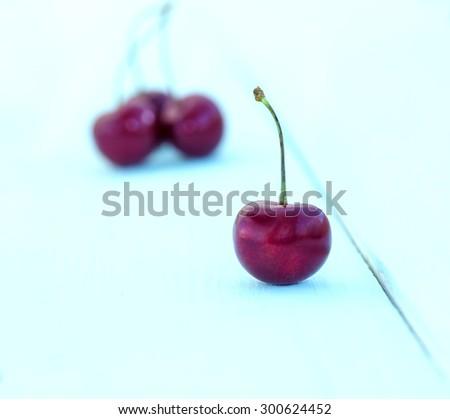 Ripe cherries. Ripe cherries on blue white wooden table. Berry ripe cherries on wooden blue table background - stock photo