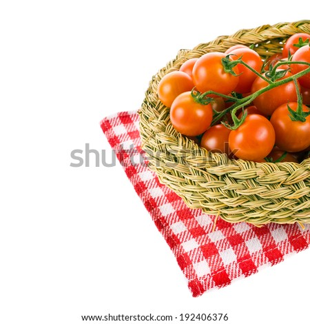 ripe cherry tomato varieties in a wicker basket on a towel round checkered red  isolated on white background - stock photo