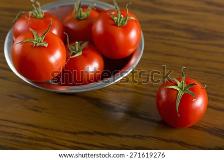 Ripe cherry tomatoes in metal bowl on wooden background - stock photo