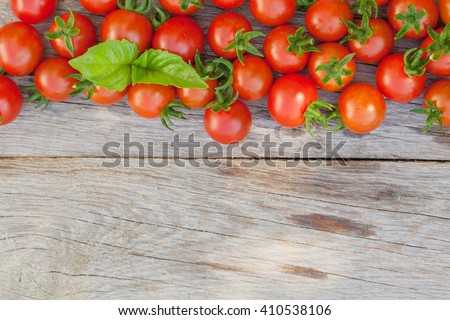 Ripe cherry tomatoes texture and basil leaves on wooden table. Top view with copy space - stock photo