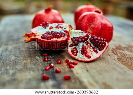 ripe cracked raw pomegranates on a dark wooden background - stock photo