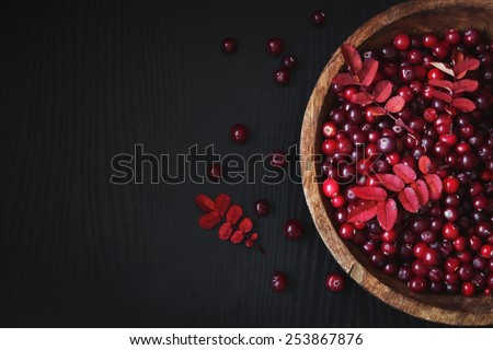 ripe cranberries in a wooden bowl on a black wooden background. health and diet food. copy space background - stock photo