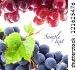 Ripe dark and red grapes with leaves, on white background - stock photo