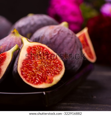 Ripe delicious figs and autumn flowers on black wooden background. Toned square image. Selective focus