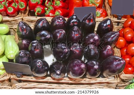 ripe eggplants on a market - stock photo