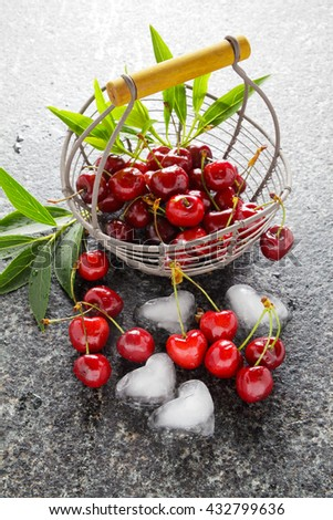 ripe fresh Cherries in the iron basket and ice cubes in the shape of Heart . Summer morning . healthy breakfast - stock photo